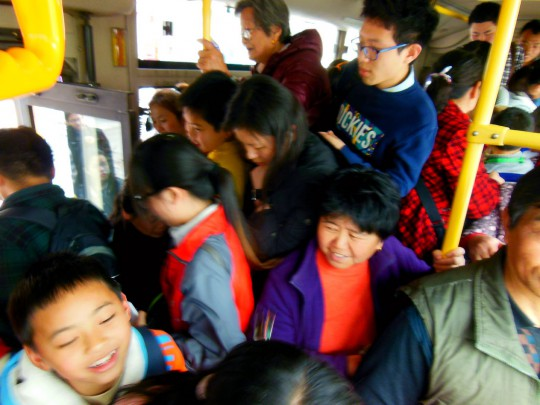 People and kids on the #3 Bus, SongJiang, Shanghai, China.